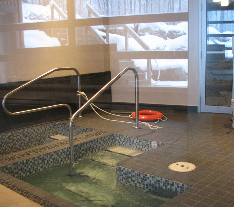 This photo of the Kneipp bath for legs (on the left) and polar bath was taken through the glass wall of the relaxation room. The reflection shows the stairs leading to one of the outdoor hot tub.
